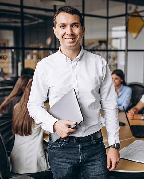 Szczęśliwy przedsiębiorca uśmiecha się w biurze