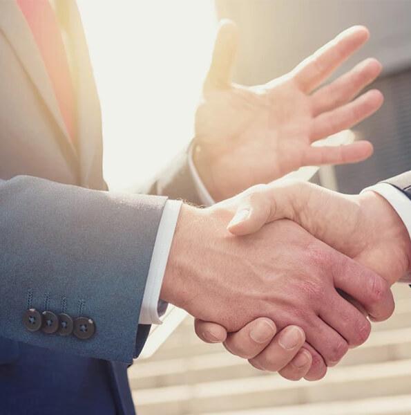 Mężczyźni w garniturach podają sobie ręce