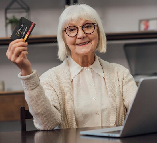 Uśmiechnięta starsza Pani siedzi przed komputerem z kartą lexnonstop