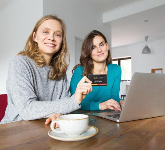 Dwie młode zadowolone kobiety siedzą przy stole i pokazują kartę lexnonstop